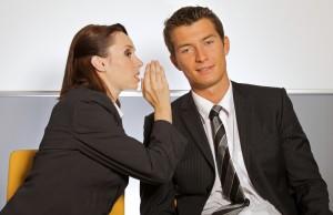 woman-whispering-secret-in-man's-ear