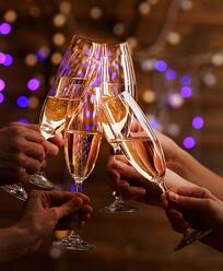 people-holding-champagne-glasses-cheers