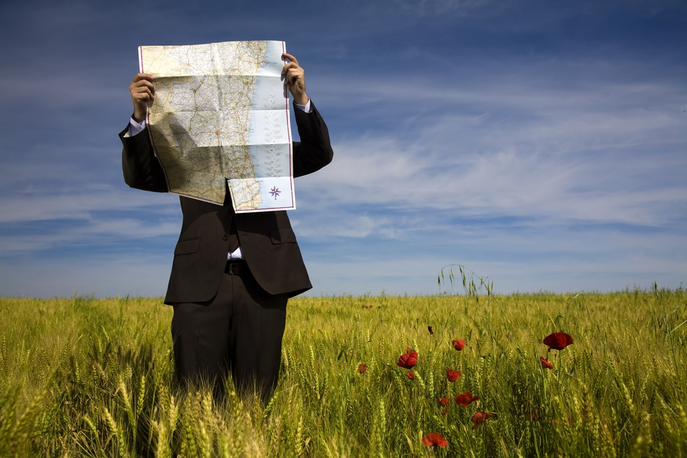 man lost with map in field