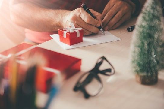 Man writes a holiday greeting card