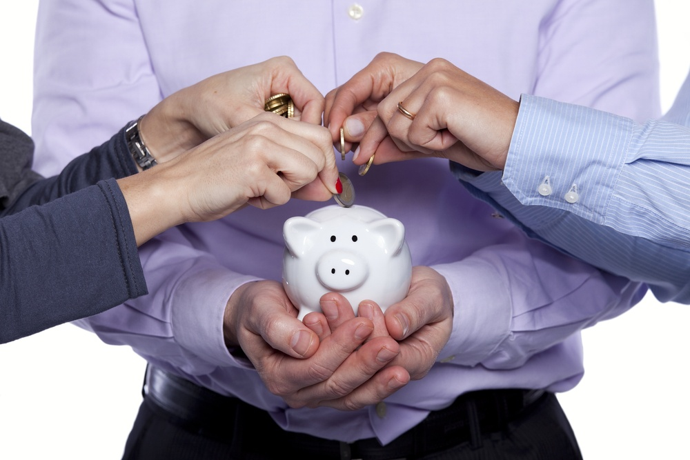people add coins to piggy bank.jpg