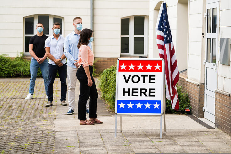 Four people lining up to vote with masks